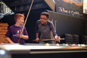 Big for a Day credit union volunteer and little playing pool