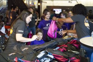 Big for a Day Desert financial credit union volunteers giving backpacks to waiting littles